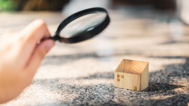 虫眼鏡を持って家のモデルを見ている手 Premium写真