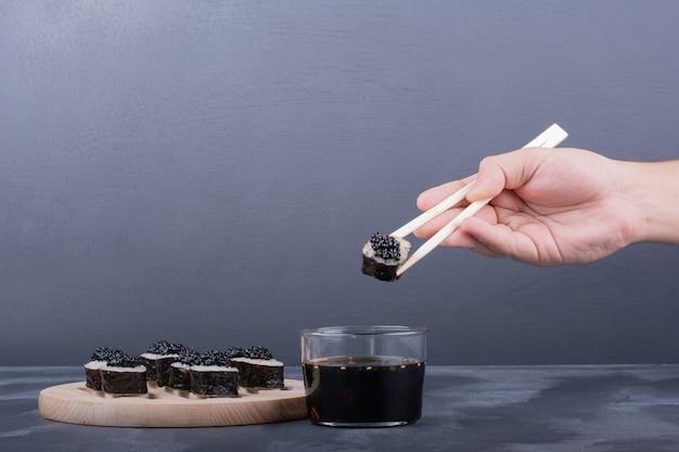 大理石に箸で巻き寿司を持っている手。 無料写真