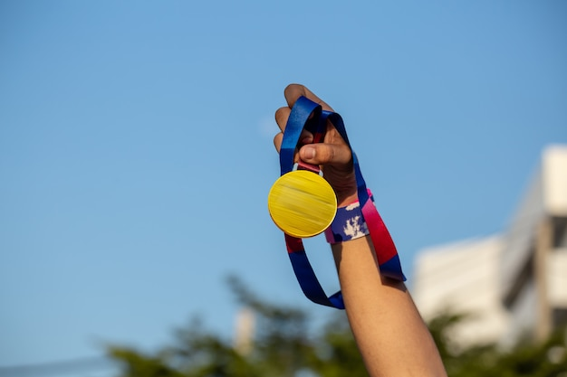 Hand holding medal outdoors Premium Photo