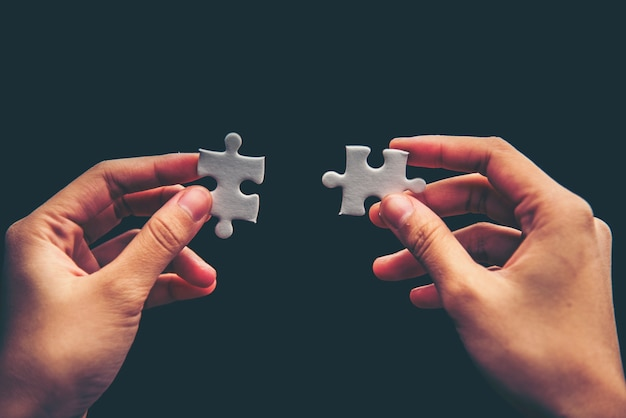 Hand holding missing jigsaw puzzle piece down Premium Photo