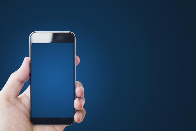 Hand holding mobile smart phone, blank blue screen on gradient blue Premium Photo