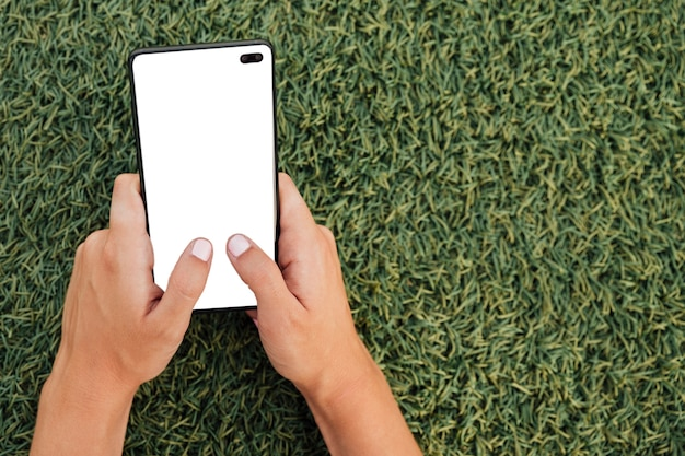 Hand holding modern smartphone with mock-up Free Photo