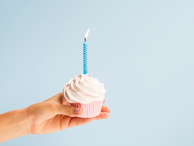 Hand holding muffin with blue candle Free Photo