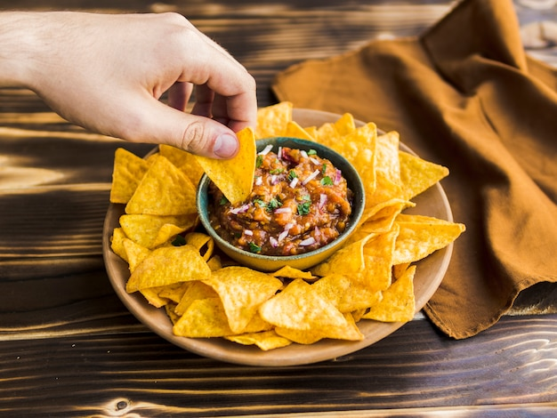 Hand holding nacho in cup of garnish Free Photo