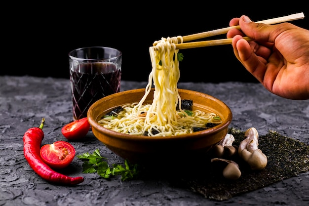 Hand holding noodles with chopsticks Free Photo