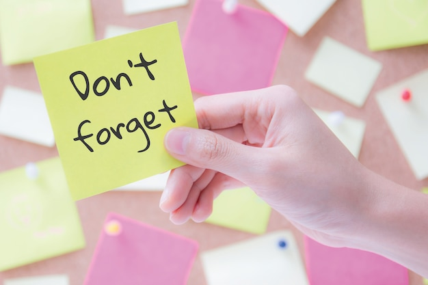 Hand holding a notepaper or post it with words don't forget Premium Photo