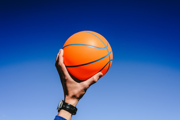 Hand holding an orange basketball ball on blue sky background, invitation to play Premium Photo