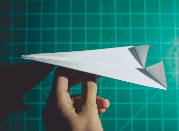 Hand holding a paper airplane engineering background Free Photo