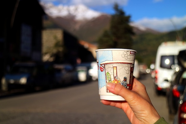 Hand holding a paper cup of coffee with blurry countryside Premium Photo