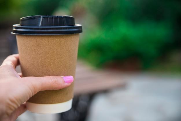 Рука, проведение бумажный стакан кофе на фоне естественного утра Бесплатные Фотографии