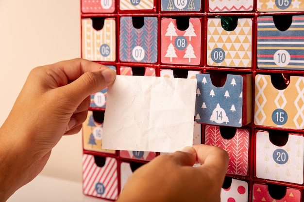 Hand holding paper sheet in front of advent calendar Free Photo