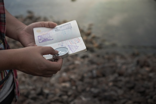 Hand holding a passport of the compass to find travel destinations. vintage style. Premium Photo