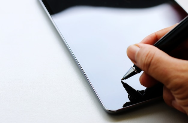Hand holding pen on tablet,copy space. Premium Photo