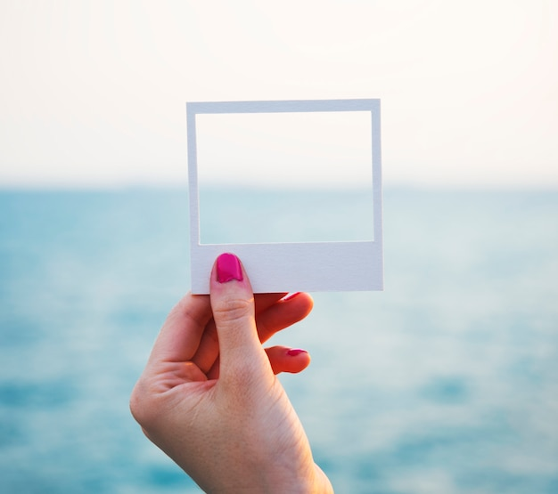 Hand holding perforated paper frame with ocean background Free Photo