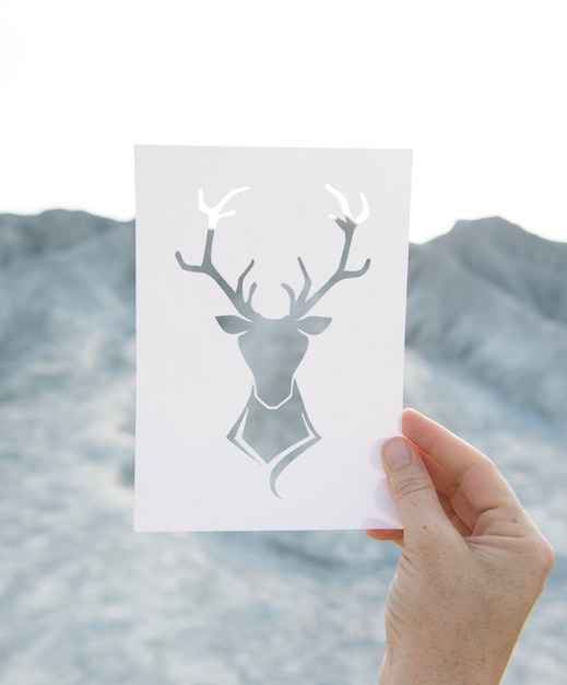 Hand holding perforated paper moose art with mountain background Free Photo