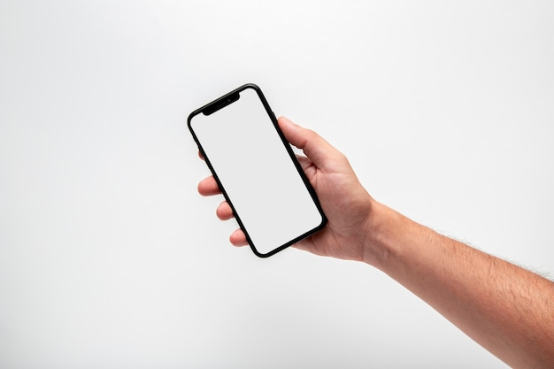 Hand holding phone mock-up Free Photo