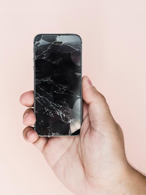 Рука держит телефон с разбитым экраном Premium Фотографии