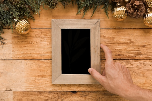 Hand holding photo frame near coniferous twigs and christmas balls Free Photo