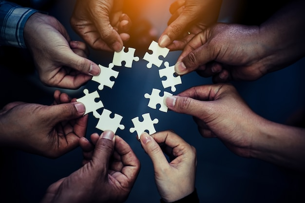 Hand holding piece of blank jigsaw puzzle with paper frame background. Premium Photo