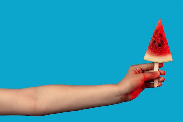 Hand holding a piece of watermelon on a stick like ice cream on blue Premium Photo