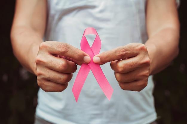 Hand holding pink ribbon Premium Photo