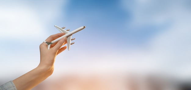 Hand holding a plane over blurred city   with sky.tourism or travel Premium Photo