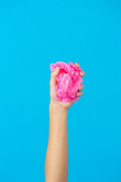 Mano che tiene il sacchetto di plastica su sfondo blu Foto Gratuite