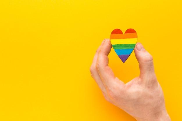 Mano che tiene un cuore arcobaleno Foto Gratuite