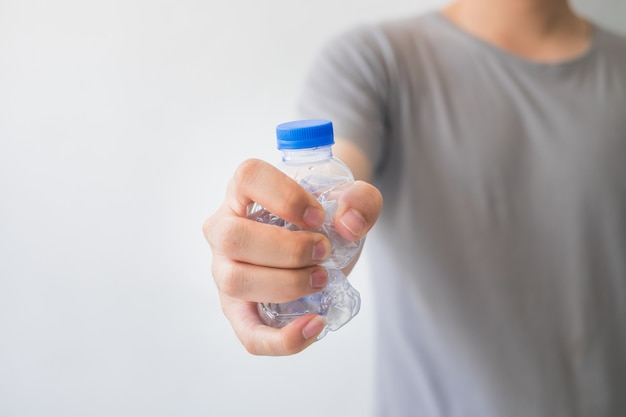 Hand holding a recyclable plastic bottles on white background. Premium Photo