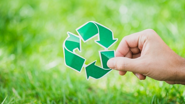 Hand holding recycle symbol against green grass Free Photo