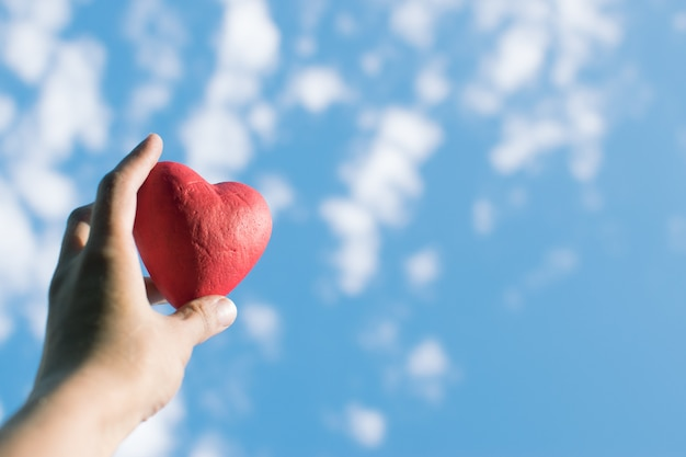 Hand holding the red decorative heart against the blue sky. Premium Photo