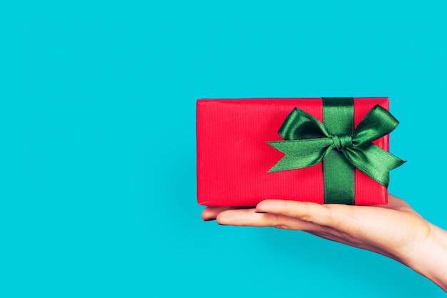 Hand holding a red gift with green bow Free Photo