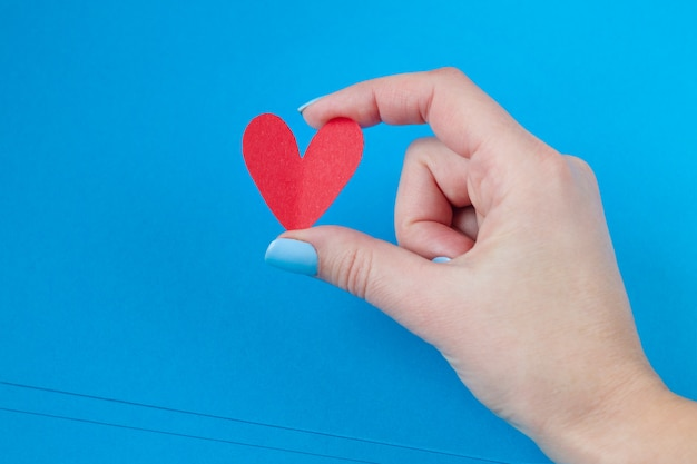 Hand holding a red heart on a blue background. background for valentine's day Premium Photo