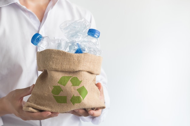 Hand holding sack bag with garbage recycle plastic bottles, global warming solution. Premium Photo