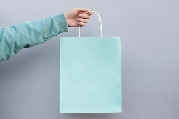 Hand holding a shopping paper bag Free Photo