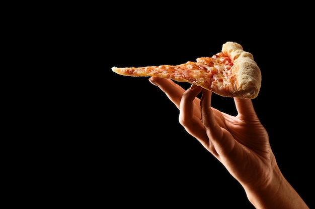 Hand holding slice of cheese pizza cut in slices Premium Photo
