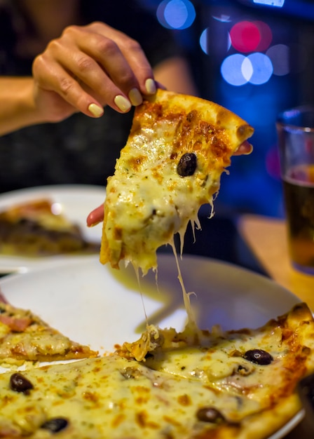 Hand holding slice of pizza Premium Photo