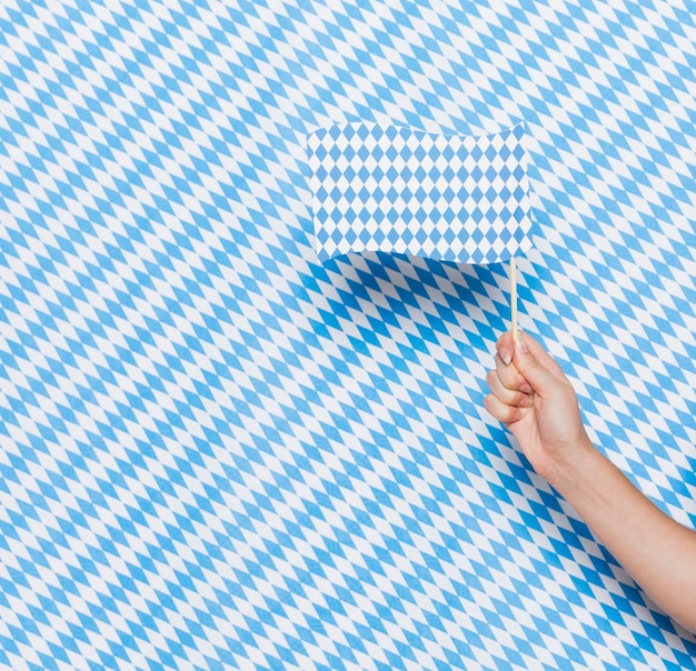 Hand holding small flag with pattern background Free Photo