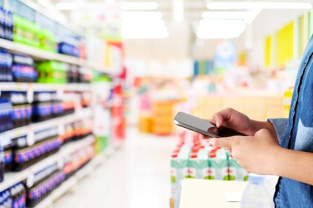 Hand holding smart phone over blur supermarket store background Premium Photo