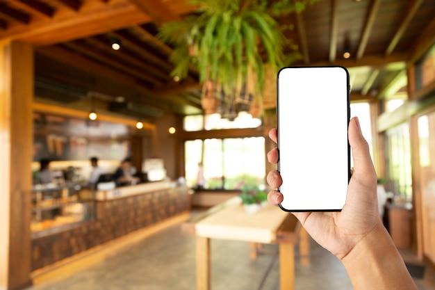 カフェでスマートフォンの空白の画面を持っている手。 Premium写真