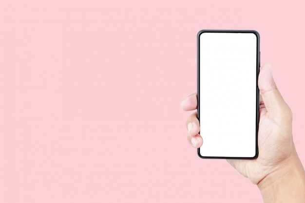 Hand holding smartphone mockup on pink pastel background with copy space Premium Photo