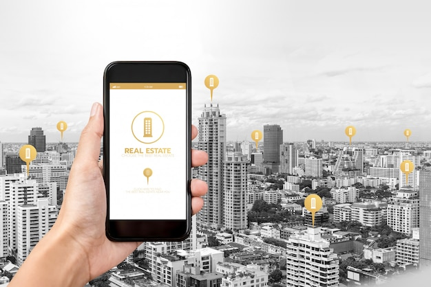 Hand holding smartphone with application to find  real estate on screen Premium Photo