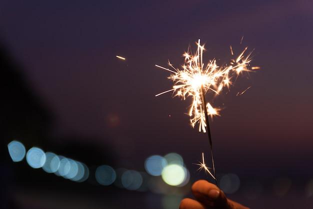 Hand holding a sparkler on beach during sunset. celebration concept. Premium Photo