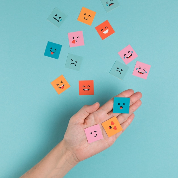Hand holding squared smiling faces Free Photo