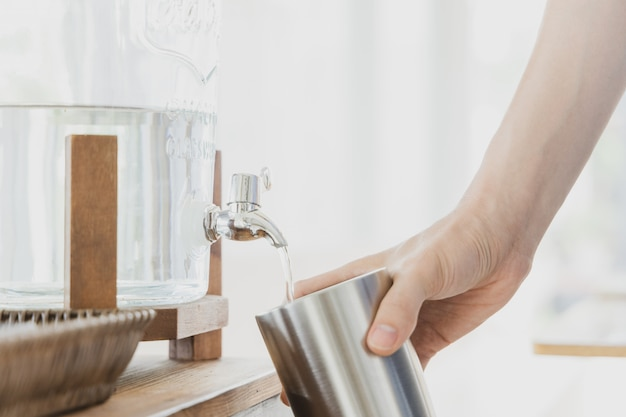 Hand holding stainless steel tumbler while filling drinking water. Premium Photo