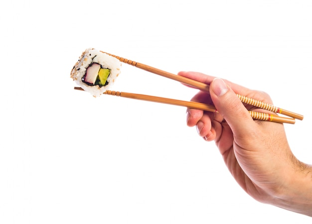 Hand holding sushi with chopsticks Free Photo