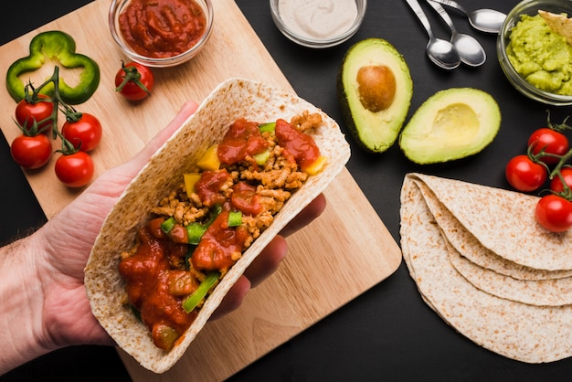 Hand holding taco near cutting board among vegetables and sauces Free Photo