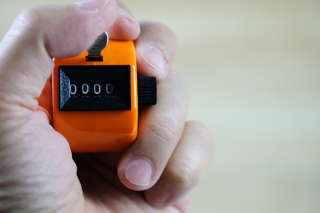 Hand holding tally counter or counting machine Premium Photo