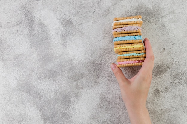 Hand holding tasty cookies on grey background Free Photo