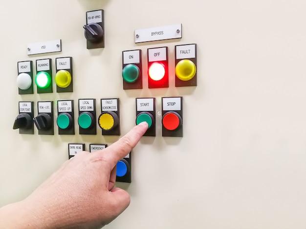 Держа рукой панель управления промышленного предприятия и нажимая или поворачивая кнопку в электрическом селекторном переключателе, кнопочный переключатель, шкаф центра управления двигателем Premium Фотографии